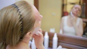 Mesotherapy在家 女孩mesorollerom处理房子的面孔在镜子前面的 影视素材