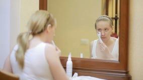 Mesotherapy在家 女孩mesorollerom处理房子的面孔在镜子前面的 股票视频