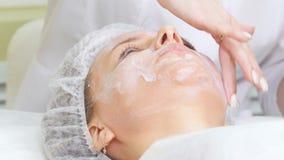 Mesotherapy Cosmetologist που εφαρμόζει την κρέμα στο πρόσωπο του πελάτη που κάνει τον καλλυντικό καθαρισμό διαδικασιών του προσώ φιλμ μικρού μήκους