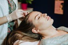 Mesotherapy Kvinna i cosmetologykabinett Cosmetologisten gör injektionen kvinnan mottar en injektion i huvudet mot som kroken för Arkivfoton