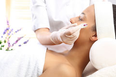 Mesotherapy microneedle, the woman at the beautician. Beautician performs a needle mesotherapy treatment on a woman's face Royalty Free Stock Images