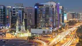 A mesquita perto de Dubai Creek cercou em construções modernas e o dia ocupado da rua do tráfego ao timelapse da noite vídeos de arquivo