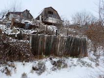 Mess an abandoned house and a fence in winter.  royalty free stock photo