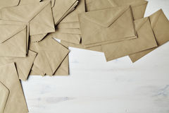 Mess of brown kraft paper post envelope on wood table Stock Photos