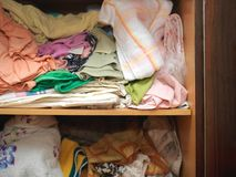 Mess in a closet. Crumpled linen and towels on a shelf of closet in complete mess, indoors close-up stock photo