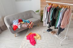 Mess in dressing room with sofa. Renew wardrobe stock image