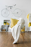 Mess left on armchair. Yellow pillow and white blanket left on white armchair in lounge Stock Photo