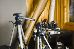 Mess in Photo Studio. Photo studio with focus on tripods in the foreground, indoor shot Royalty Free Stock Photo