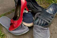 Mess of various footwear. With a red high hell on the top, outdoor close-up royalty free stock image