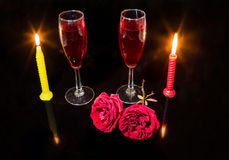 Messa a punto romantica con le rose rosse brucianti delle candele ed i vetri del vino rosso nel fondo scuro Immagine Stock Libera da Diritti