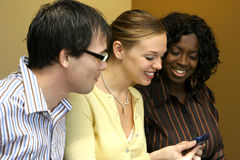 Message. Group of young professionals looking at a handheld Royalty Free Stock Photo