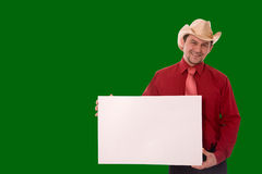 Message. Cowboy holding empty message board over green Stock Image