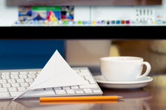 Message arrived. Paper airplane on the keyboard. PC display at background Royalty Free Stock Photos