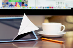 Message arrived. Paper airplane on the tablet. PC display and coffee cup at background Stock Images
