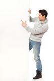 Message on the banner. Handsome man in jeans and gray sweater pointing at a banner. Full length studio shot isolated on white Stock Images