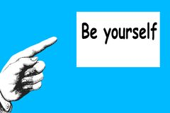 `Be Yourself`. The direction of the finger points to a motivational and inspirational message. The message `Be yourself` written whit black letters in the white stock image
