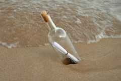 Message in a bottle 1. Message in a bottle buried in the sand stock images