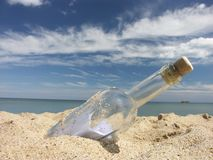 Message in the bottle. Washed ashore, with ship away on the horizon line royalty free stock image