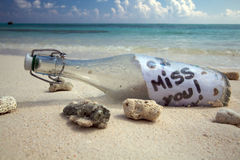 A Message in a Bottle!. Message in a bottle on a tropical beach saying 'I miss you Stock Photography