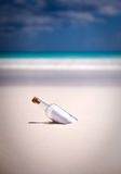 Message in a bottle. A message in a bottle on a white sand beach Stock Images