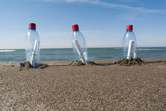 Message in a bottle. Three messages in three plastic bottles Royalty Free Stock Photo