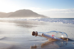 Message in a Bottle. A message inside a glass bottle, washed up on a remote beach Stock Photography