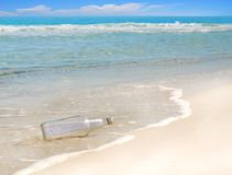 Message in the Bottle. Mysterious message in a bottle washed up on gorgeous beach stock photo