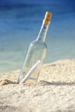 Message In Bottle. Message in a bottle on an isolated beach royalty free stock image