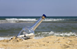 Message in a bottle on the beach. Bottle with a letter on the beach royalty free stock photos