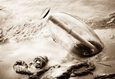 Message in bottle on the beach. Bottle with a letter out of water royalty free stock image
