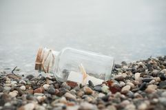Message in a bottle on the beach. Closeup of message in a bottle on the beach Stock Photo