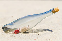 Message in a bottle on the beach. Closeup of message in a bottle on the beach Royalty Free Stock Image