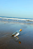 Message in a bottle on the beach. Bottle found on the beach with a message inside Royalty Free Stock Image