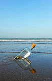 Message in a bottle on the beach. Bottle found on the beach with a message inside Stock Images