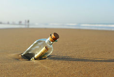 Message in a bottle on the beach. Bottle found on the beach with a message inside Royalty Free Stock Photos
