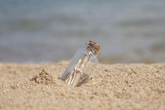 Message in a bottle on beach. Message in a small bottle on a sandy beach royalty free stock photography