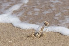 Message in a bottle on beach. Message in a small bottle on a sandy beach stock photo