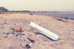 Message in a bottle on a beach. In the summer Royalty Free Stock Photo