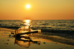 Message in a bottle on beach at sunrise. Wall art and home decoration royalty free stock photography