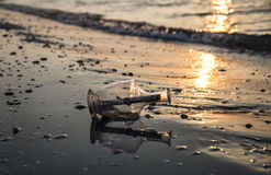 Message in a bottle on beach at sunrise Royalty Free Stock Photos