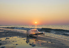 Message in a bottle on beach at sunrise. Wall art and home decoration stock photo