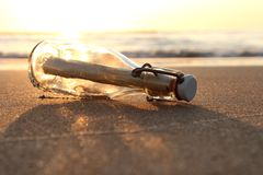 Message in a bottle. On the beach at sunset royalty free stock images