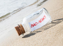Message in a bottle on beach with text Bad news Stock Image