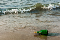 Message bottle on beach in waves. Message bottle on beach sand in waves royalty free stock photo