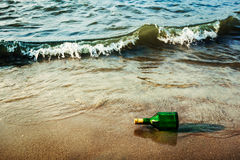 Message bottle on beach in waves. Vintage retro hipster style travel image of message bottle on beach sand in waves royalty free stock images