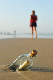 Message in a bottle on the beach, woman walking. Bottle found on the beach with a message inside Stock Photography