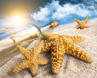 Message in a bottle buried in sand. On a beach stock photo