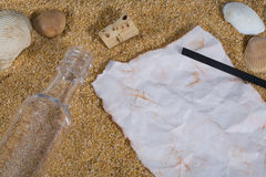 Message in a Bottle with Charcoal. Bottle and cork on sand with sea shells along with paper and charcoal for writing message Royalty Free Stock Images