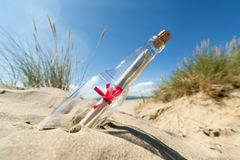 Message in a bottle. Message in a clear glass bottle washed up on the beach concept for sos, assistance, help and stranded Stock Photos