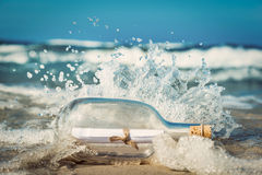 Message in the bottle coming with wave from ocean. Concept of travel, romantic secret, marine Royalty Free Stock Photos